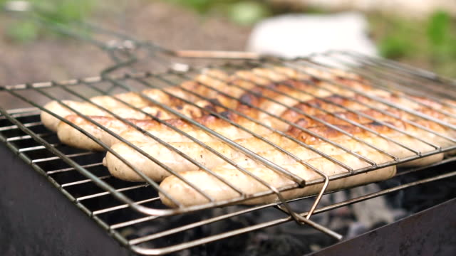 Delicious pork sausages grilling outdoors