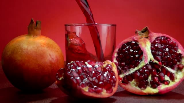 Delicious red pomegranate juice wave is falling into a small glass - video