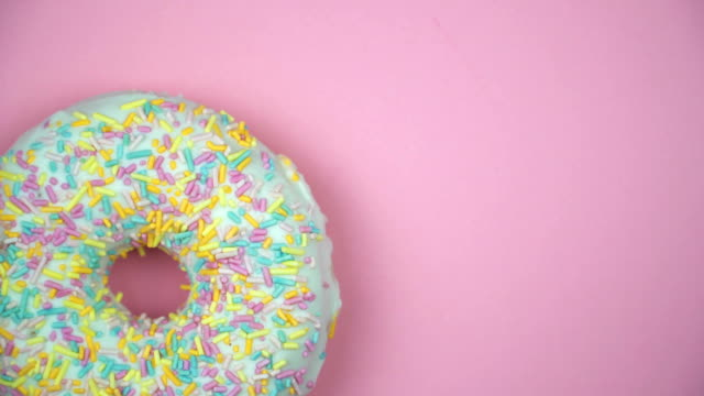delicious sweet donut rotating on a plate. top view. bright and colorful sprinkled donut close-up macro shot spinning on a pink background - decorazione per dolci video stock e b–roll