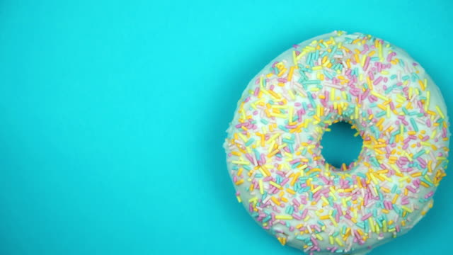 delicious sweet donut rotating on a plate. top view. bright and colorful sprinkled donut close-up macro shot spinning on a blue background - decorazione per dolci video stock e b–roll