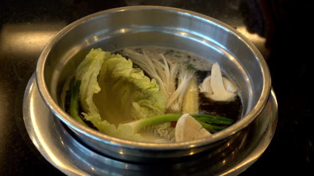 Delicious thai food soup cooking with hand vegetable seafood and meat in restaurant. video