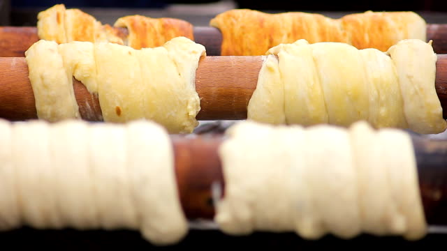 Delicious trdelnik browning on wooden sticks at high temperature, Czech cuisine video