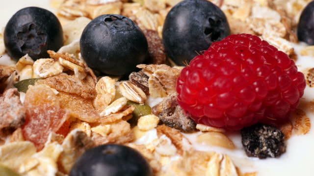 Delicious yogurt breakfast bowl with muesli and fresh berries video