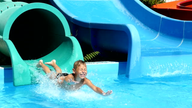 Delight the child on the water slides in the water park (slow motion) video