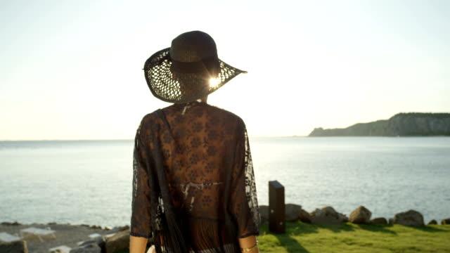 SLOW MOTION: Delighted girl running towards magical sunrise above stunning ocean