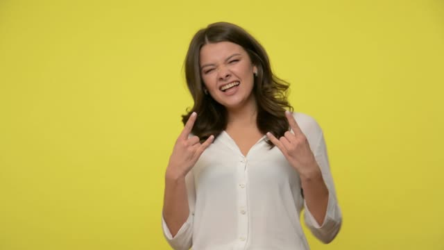 Delighted overjoyed brunette girl in blouse showing rock n roll gesture by hands, cool sign, and shouting yeah with crazy expression