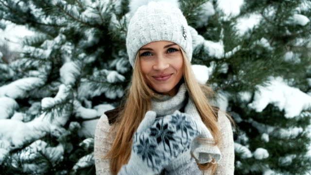 Delightful blonde smiles against background of snow-covered landscape video