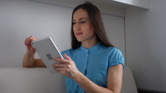 Delightful female sitting on the sofa and browsing an internet via tablet video