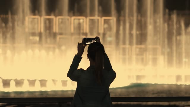 delightful young tourist girl takes photos and videos of fountains - dubai video stock e b–roll