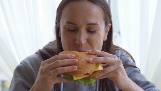 delighthed woman tasting a big hamburger at home - голодный стоковые видео и кадры b-roll