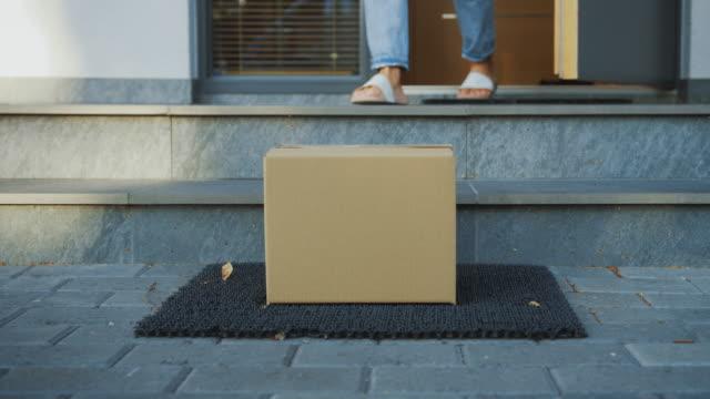 vídeos de stock, filmes e b-roll de entregue o pacote da caixa de cartão no patamar, mulher anônima sai da porta e pega sua parcela postal. tiro nivelado do baixo nível da terra do close-up. - correio correspondência