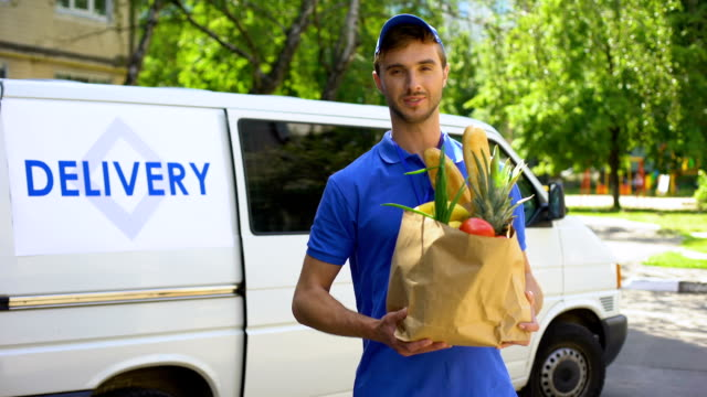 delivery company worker holding grocery bag, food order, supermarket service - icona supermercato video stock e b–roll