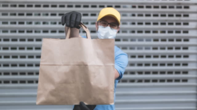 vídeos de stock, filmes e b-roll de entregador com máscara de proteção e luvas segurando caixa/saco com mantimentos em frente a um prédio. - voluntário