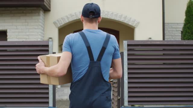 送貨員來到郊區的房子門和敲門聲。相機跟著他從後面。 - postal worker 個影片檔及 b 捲影像