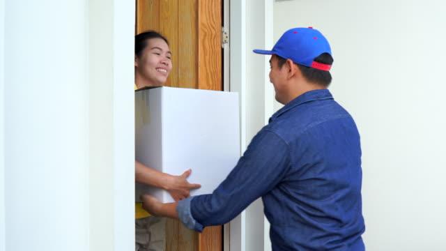 vídeos de stock e filmes b-roll de delivery man in blue uniform hand parcel box to recipient - door knock
