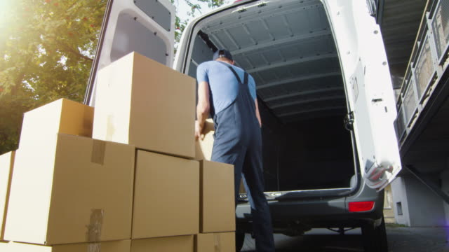 Delivery Man Loads Cardboard Boxes into his Van. Slow Motion. Delivery Man Loads Cardboard Boxes into his Van. Slow Motion. Shot on RED Cinema Camera in 4K (UHD). vänskap stock videos & royalty-free footage