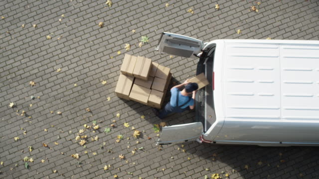 Delivery Man Loads his Commercial Van with Cardboard Boxes. Speed up Video. Delivery Man Loads his Commercial Van with Cardboard Boxes. Speed up Video. Shot on Camera in 4K (UHD). post structure stock videos & royalty-free footage