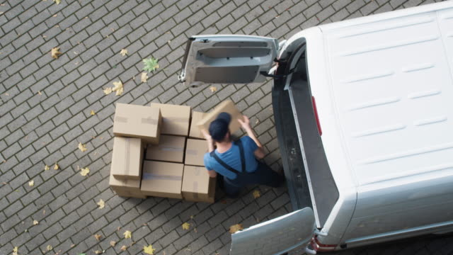 delivery man loads his commercial van with cardboard boxes. speed up video. - furgone video stock e b–roll