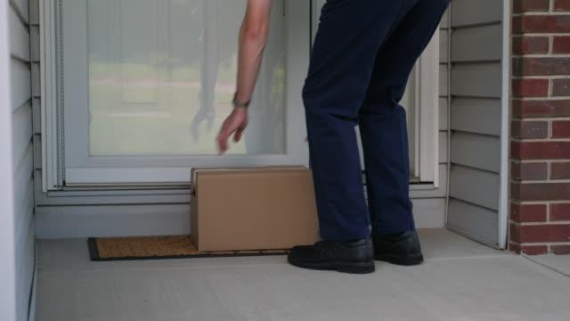 vídeos de stock e filmes b-roll de delivery man places cardboard box on residential front porch - entregar