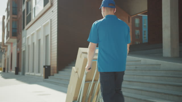 Delivery Man Pushes Hand Truck Trolley Full of Cardboard Boxes, Packages For Delivery. Professional Courier Working Efficiently, Quickly. Walks Through Stylish Modern Urban Area. Following Back View Delivery Man Pushes Hand Truck Trolley Full of Cardboard Boxes, Packages For Delivery. Professional Courier Working Efficiently, Quickly. Walks Through Stylish Modern Urban Area. Following Back View post office stock videos & royalty-free footage