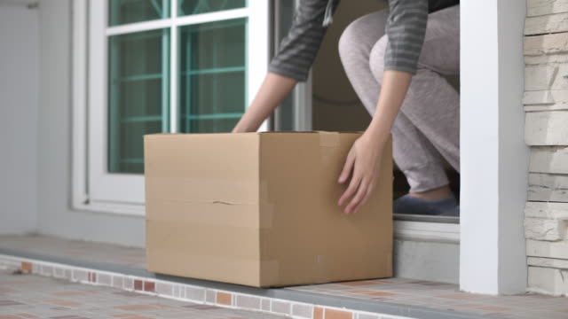 delivery man put package on doorstep - portico video stock e b–roll