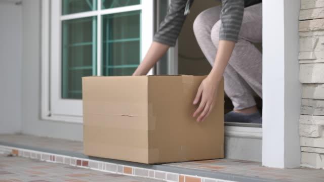 vídeos de stock e filmes b-roll de delivery man put package on doorstep - cardboard box