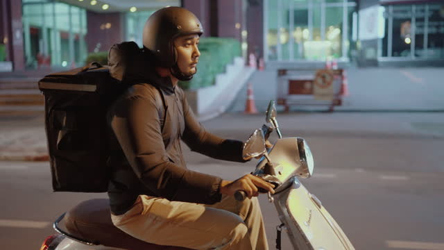 Delivery man riding a motorcycle in the city at night Asian food courier delivering orders in Bangkok motorcycle stock videos & royalty-free footage