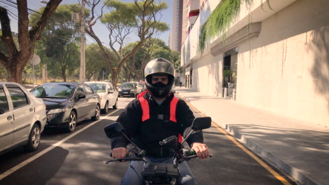 Delivery man riding a motorcycle - motoboy Delivery man riding a motorcycle - motoboy motorcycle stock videos & royalty-free footage