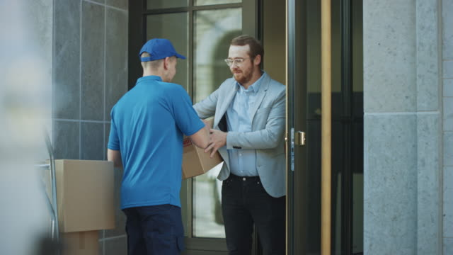 delivery man takes postal package from a customer who signs electronic signature pod device. loads delivery into his truck / van. in business district courier takes cardboard box parcel from a man - inviare video stock e b–roll