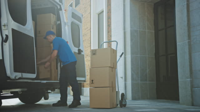 Delivery Man Uses Hand Truck Trolley Full of Cardboard Boxes and Packages, Loads Parcels into Truck / Van. Professional Courier / Loader helping you Move, Delivering Your Purchased Items Efficiently video