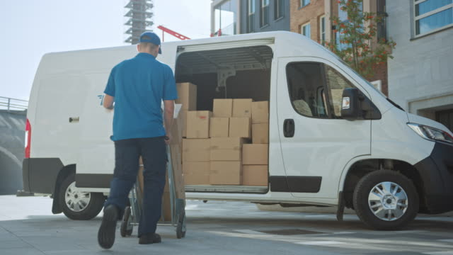 Delivery Man Uses Hand Truck Trolley Full of Cardboard Boxes and Packages, Loads Parcels into Truck / Van. Professional Courier / Loader helping you Move, Delivering Your Purchased Items Efficiently - vídeo