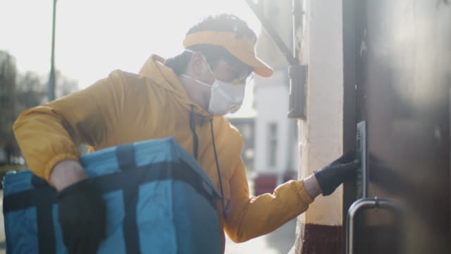 delivery man wearing protective mask and rubber gloves checking address in his smartphone - food delivery filmów i materiałów b-roll