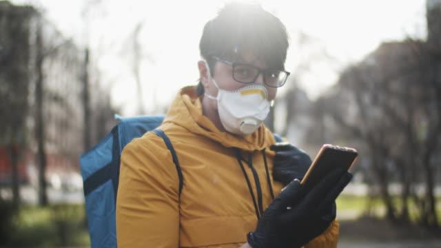 liefermann trägt schutzmaske und gummihandschuhe überprüfen adresse in seinem smartphone - smartphone mit corona app stock-videos und b-roll-filmmaterial
