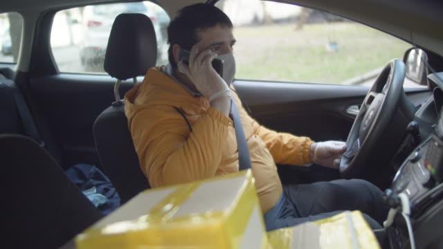 liefermann trägt schutzmaske und gummihandschuhe sprechen auf dem smartphone - smartphone mit corona app stock-videos und b-roll-filmmaterial