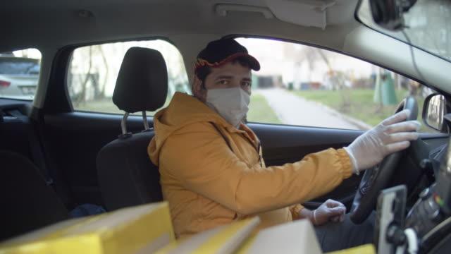 在疾病流行期間,送貨員戴著防護面具和橡膠手套,帶包裹停車 - postal worker 個影片檔及 b 捲影像
