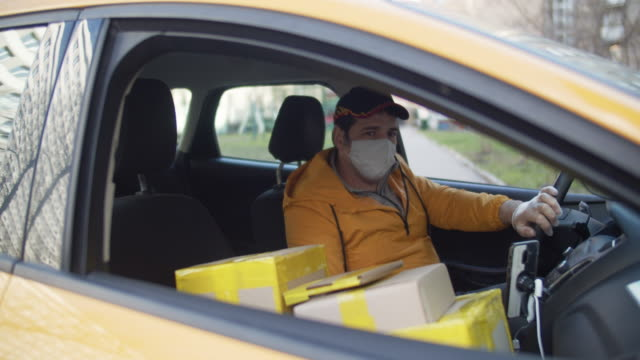 Delivery man wearing protective mask and rubber gloves with parcels parking car during an illness epidemic Man delivering package, shot using BMPCC 4k post office stock videos & royalty-free footage