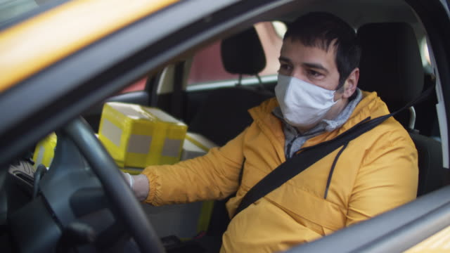 Delivery man wearing protective mask and rubber gloves with parcels in car during an illness epidemic Man delivering package, shot using BMPCC 4k post office stock videos & royalty-free footage