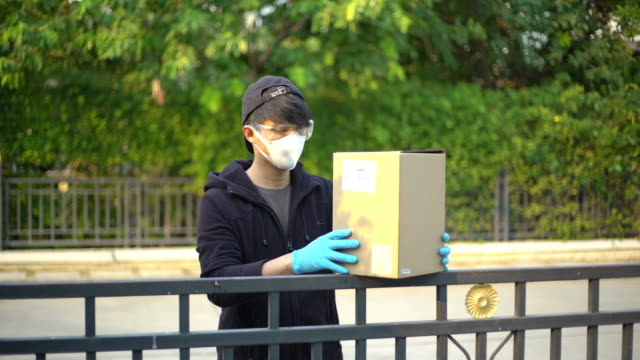 delivery man wearing safety glasses and face mask putting down the package on the fence and keep distance reduce germ spread - essential workers stock videos & royalty-free footage