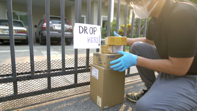 Delivery man wearing safety glasses and face mask putting down the package outside the fence for keeping distance reduce germ spread