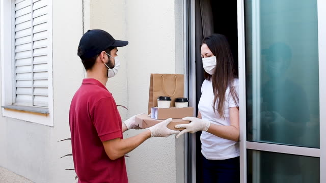 vídeos de stock e filmes b-roll de delivery man with gloves and masks delivering food. food delivery concept. - covid restaurant