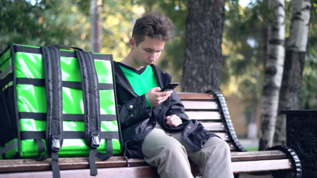 緑色のバックパックと自転車を持つ配達人は、電話でクライアントのアドレスを探しています。 ビデオ