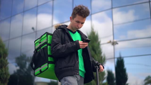 緑のバックパックとスクーターを持つ配達人は、電話でクライアントのアドレスを探しています ビデオ