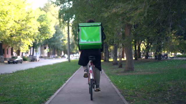 緑のバックパックを持つ配達人は、食品配達と市内を自転車に乗ります ビデオ