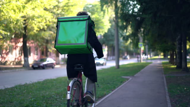 delivery man with green backpack rides a bicycle through the city with food delivery