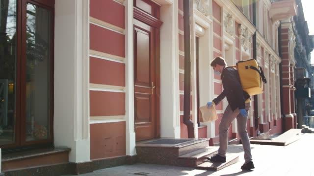 sarı bagpack ve koruyucu maske ile teslimat adam gıda ile paket sunar ve veranda, temassız teslimat konsepti üzerinde bırakın - sahanlık stok videoları ve detay görüntü çekimi