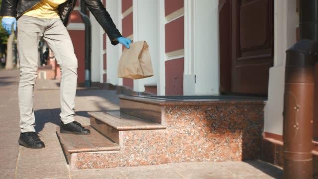 sarı bagpack ve koruyucu maske ile teslimat adam gıda ile paket sunar ve veranda, temassız teslimat konsepti, çekim yakın bırakın - sahanlık stok videoları ve detay görüntü çekimi