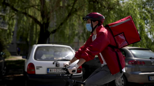 Delivery man working during coronavirus pandemic Delivery man wearing red jacket, cycling helmet, protective face mask and backpack riding bike to his next customer during coronavirus pandemic cycle vehicle stock videos & royalty-free footage