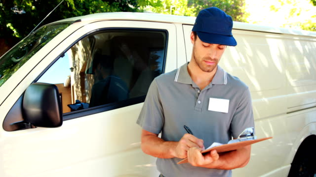 Delivery man writing on clipboard video