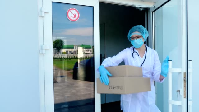 Delivery of parcel with medical equipment to hospital during coronavirus outbreak. Courier, in protective mask, gloves, leaves at entrance door some boxes for doctor to take away video
