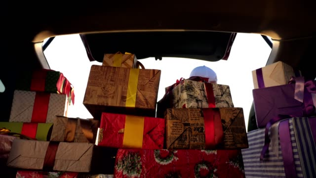leveransservice. deliveryman i skyddsmask. kurir lastar lådor. presentaskar i bil. vackert inslagna skiften. utsikt inifrån bilen. donation, välgörenhet eller leveranskoncept - christmas present bildbanksvideor och videomaterial från bakom kulisserna